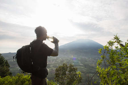 Hiking man relaxing and drinking water from bottle on top of the mountain back