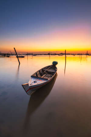 beautiful sunrise on the coast of the Gulf of Batam Batam Island, Indonesia. This is a rural area where residents work as fishermen since tens of years ago. traditional boat and wooden bridge