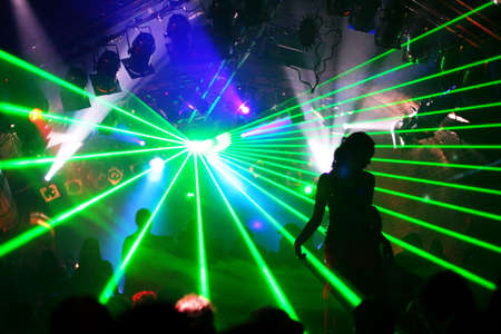 silhouette of dancing woman between green laser light Фото со стока