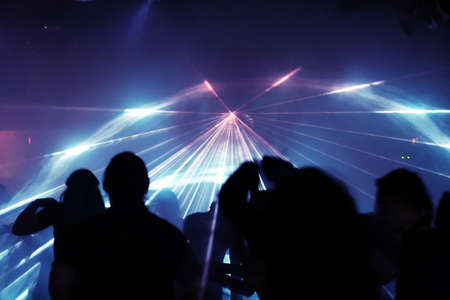 silhouettes of dancing people between laser beams