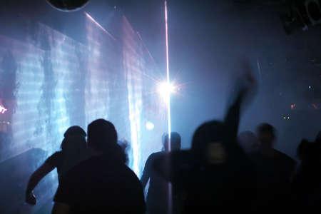 silhouettes of dancing people between laser beams