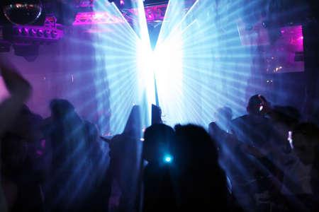 clubbers: siluetas de personas bailando entre rayos l�ser -
