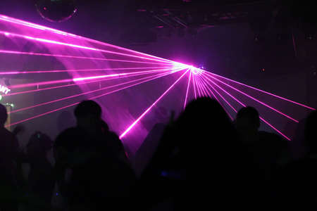 silhouettes of dancing people between laser-beams