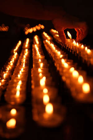 votive candle: Votive candle placed by mans hand Stock Photo