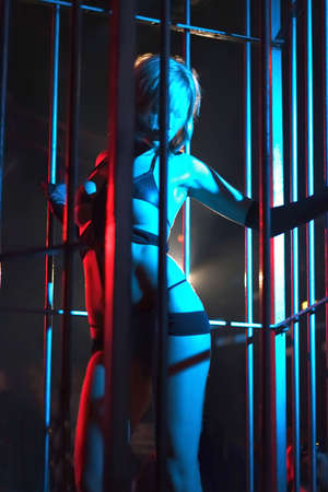 Sexy young woman Dancing in a steel cage in an underground club
