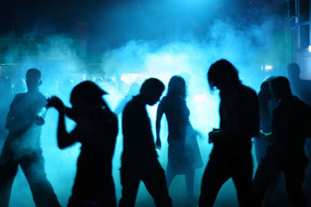 Silhouettes of a dancing teenagers in a disco Фото со стока