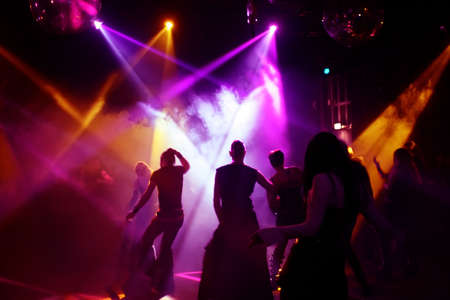 Silhouettes of a dancing teenagers in a disco Stock Photo