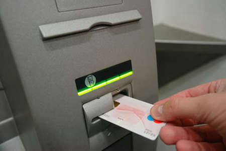 ATM Access - Males hand inserts banking card Stock Photo - 983431
