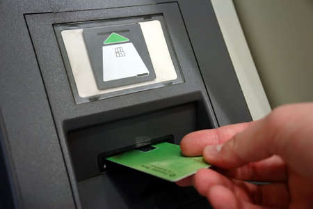 ATM Access - Males hand inserts banking card Stock Photo - 983432