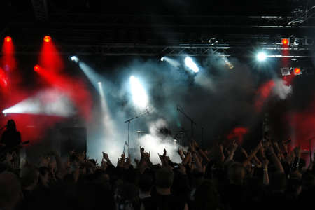 Cheering crowd at concert, musicians on the stage Stock Photo
