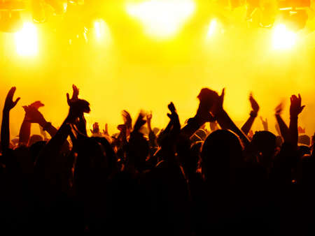 silhouettes of concert crowd in front of bright stage lights 版權商用圖片