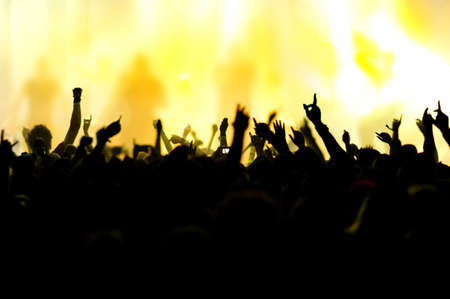 concert band: silhouettes of concert crowd in front of bright stage lights Stock Photo