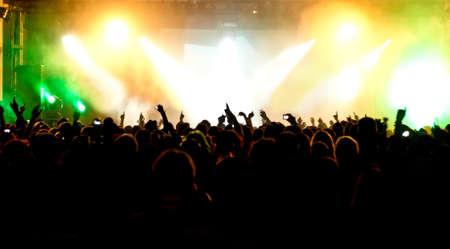 silhouetten van concert menigte in de voorkant van het podium fel licht Stockfoto