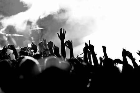 band: silhouettes of concert crowd in front of bright stage lights Stock Photo