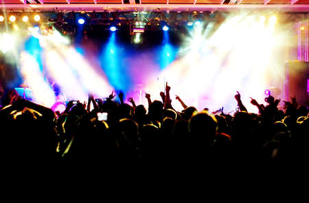 live happy: silhouettes of concert crowd in front of bright stage lights Stock Photo