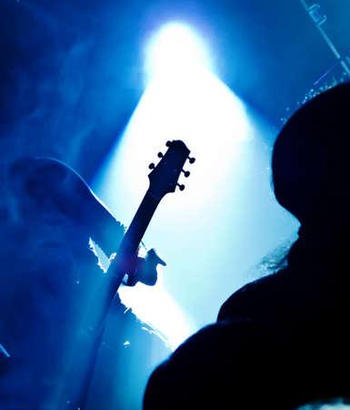 fari da palco: silhouette di chitarrista in concerto di fronte al palco luci brillanti