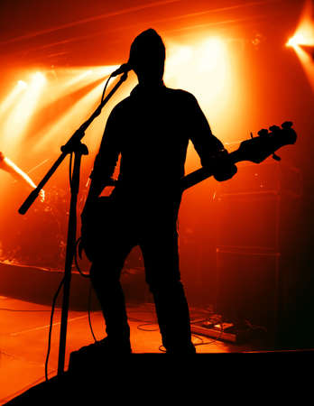 silhouette of guitar player at concert in front of bright stage lights photo