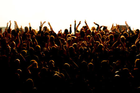 applauding: silhouettes of concert crowd in front of bright stage lights Stock Photo