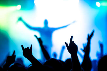 silhouettes of concert crowd in front of bright stage lights Stock Photo