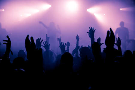concert crowd: silhouettes of concert crowd in front of bright stage lights Stock Photo