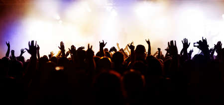crowd: silhouettes of concert crowd in front of bright stage lights Stock Photo