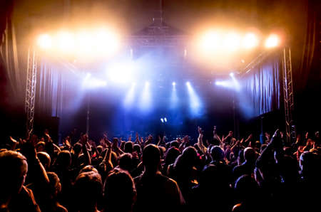 silhouettes of concert crowd in front of bright stage lights Редакционное