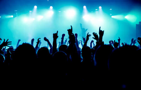 silhouettes of concert crowd in front of bright stage lights photo