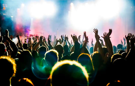 fan dance: silhouettes of concert crowd in front of bright stage lights Stock Photo