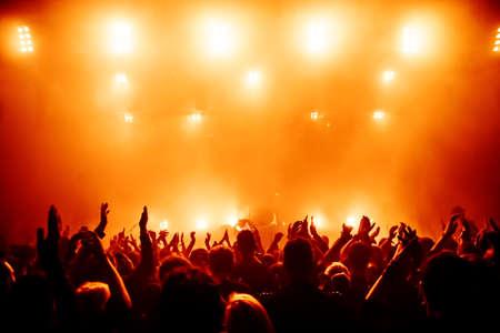 밝은 무대 조명 앞의 콘서트 군중의 실루엣