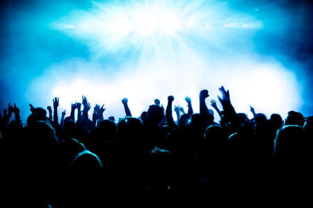 band stage: silhouettes of concert crowd in front of bright stage lights Stock Photo