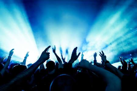 taniec: sylwetki tłumu koncertowego przed jasnym światłem scenicznych