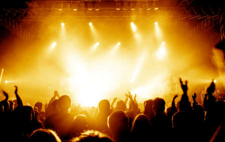 people clapping: silhouettes of concert crowd in front of bright stage lights Stock Photo