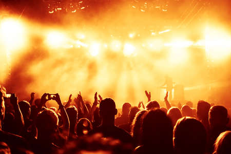 crowd of happy people: silhouettes of concert crowd in front of bright stage lights Stock Photo