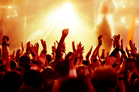 band music: silhouettes of concert crowd in front of bright stage lights Stock Photo