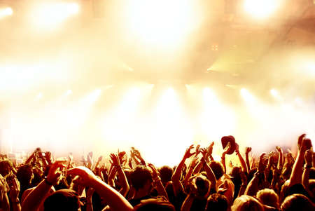 festival: silhouettes of concert crowd in front of bright stage lights Stock Photo