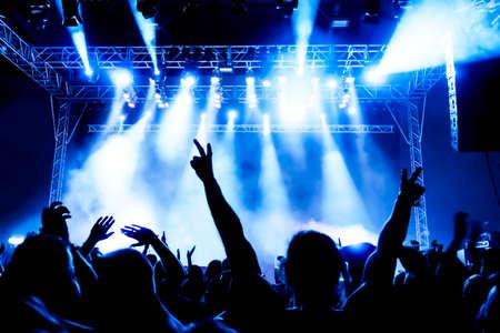 明るいライトの前に群衆のコンサートのシルエット 写真素材