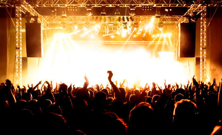 live event: silhouettes of concert crowd in front of bright stage lights Stock Photo