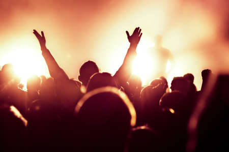 rock concert: silhouettes of concert crowd in front of bright stage lights Stock Photo