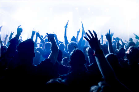 cheerful: silhouettes of concert crowd in front of bright stage lights Stock Photo