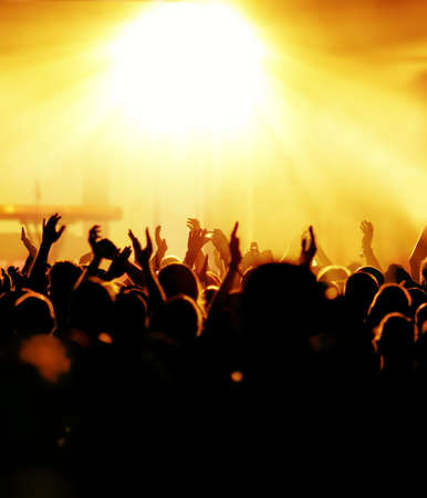 dancing disco: silhouettes of concert crowd in front of bright stage lights Stock Photo