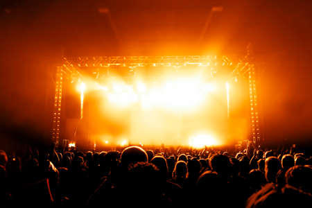 silhouettes of concert crowd in front of bright stage lights Banco de Imagens