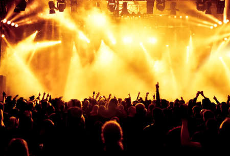 people dancing: silhouettes of concert crowd in front of bright stage lights Stock Photo