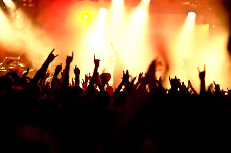 dancing club: silhouettes of concert crowd in front of bright stage lights Stock Photo