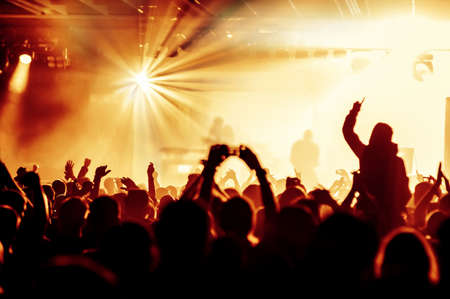 rock band: silhouettes of concert crowd in front of bright stage lights Stock Photo