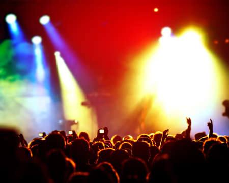 loud music: silhouettes of concert crowd in front of bright stage lights Stock Photo
