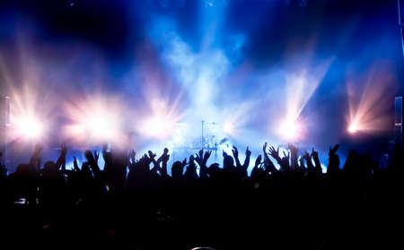 밝은 무대 조명 앞에서 콘서트 군중의 실루엣