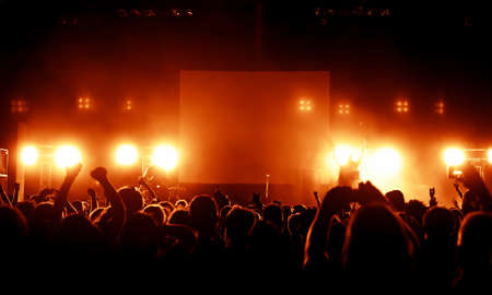 silhouettes of concert crowd in front of bright stage lights Stock fotó