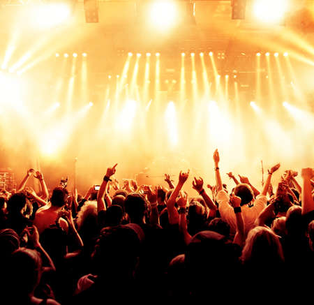 silhouettes of concert crowd in front of bright stage lights Imagens