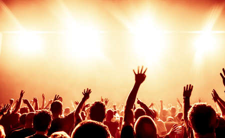 clapping: silhouettes of concert crowd in front of bright stage lights Stock Photo