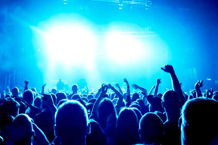 silhouettes of concert crowd in front of bright stage lights Фото со стока